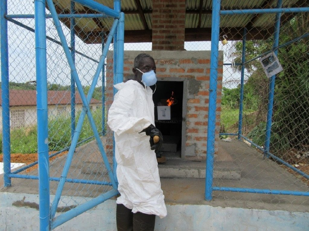 Wheagar Smith, a cleaner at Well Baby Clinic in Grand Bassa County, using the newly built incinerator