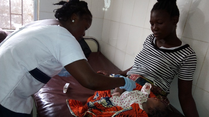 A health worker in Liberia shows a mother how to apply chlorhexidine gel to the cord site to prevent newborn sepsis