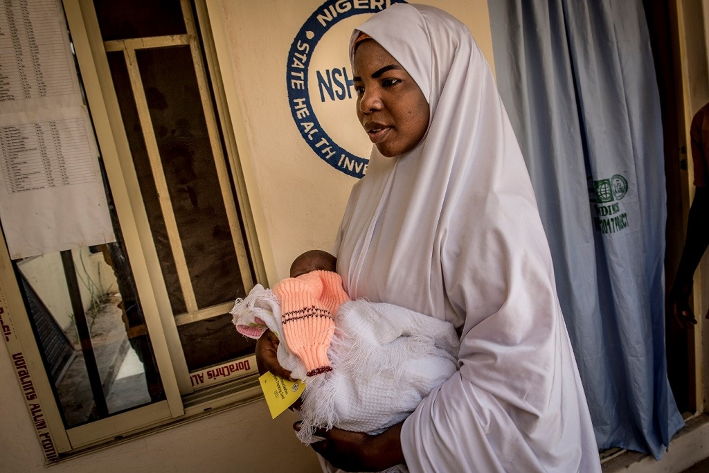 Kayya Abdulkadir arrives to Wandi Clinic with her newborn son, Mohammed, with the card she received during his shaving ceremony.