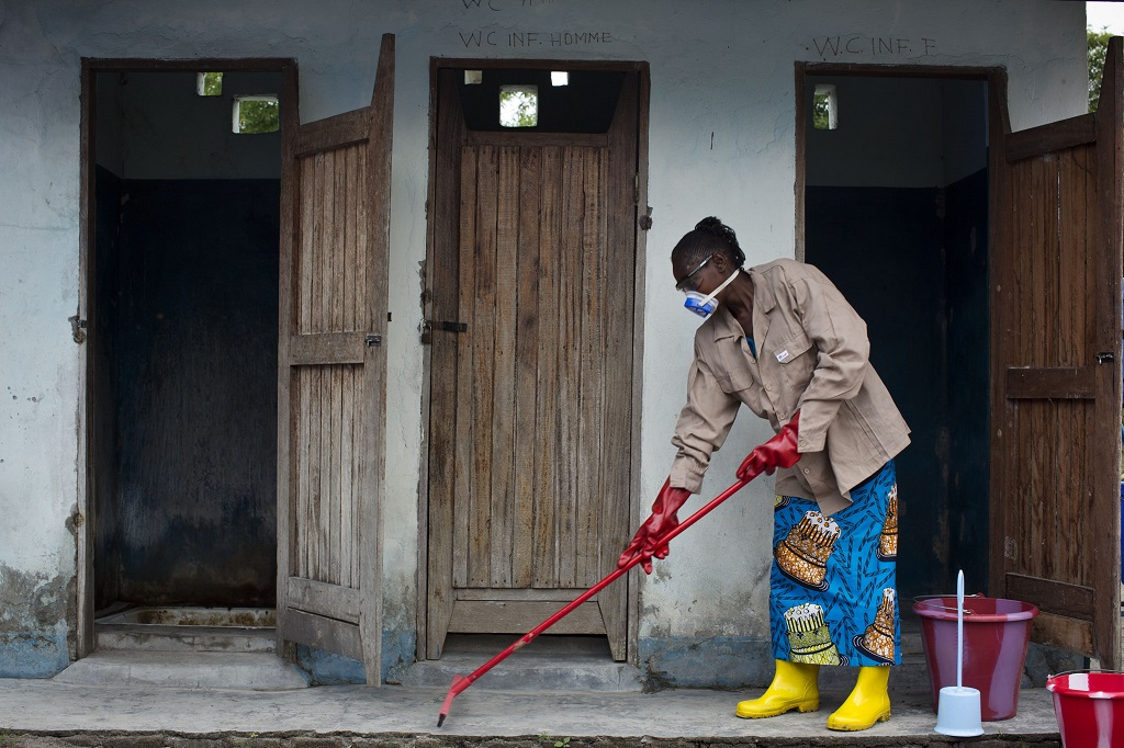cleans the latrines at a health center in DR Congo