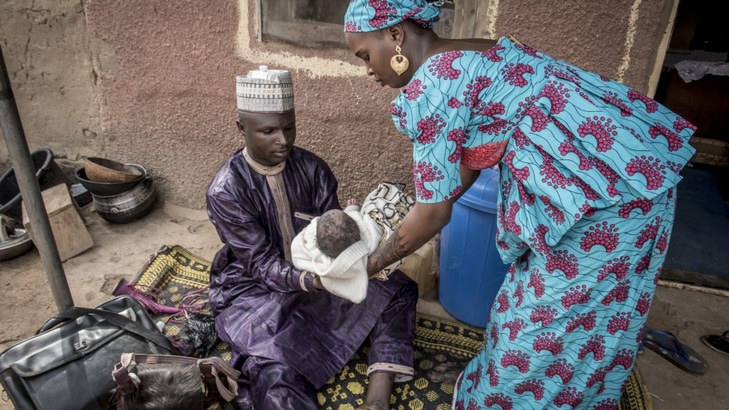 Barber Abdulaziz Lawn hands Abubakar Nafisatu to his mother, Nafisatu Bilyaminu, after shaving the newborn's head and asking his mother if he had been immunized.