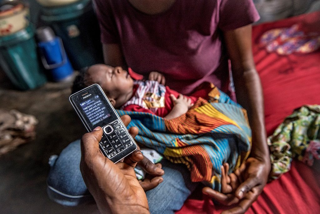 Family in Nigeria receiving health messages via mobile phone.