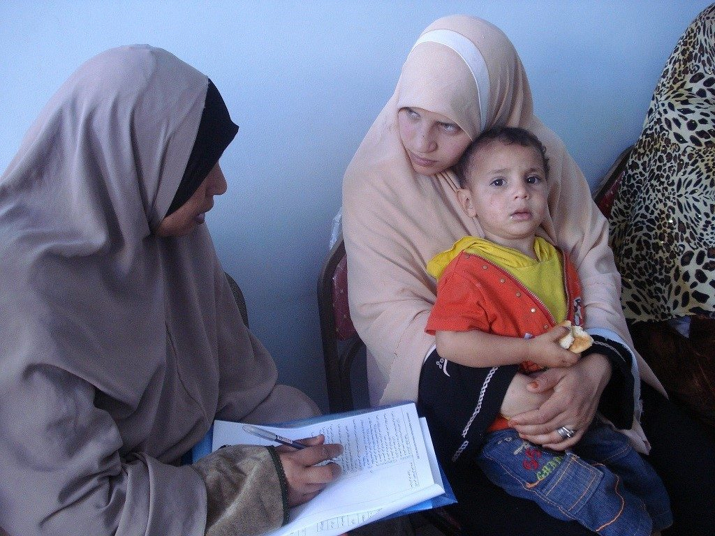 Egyptian mother holding child and talking to health worker