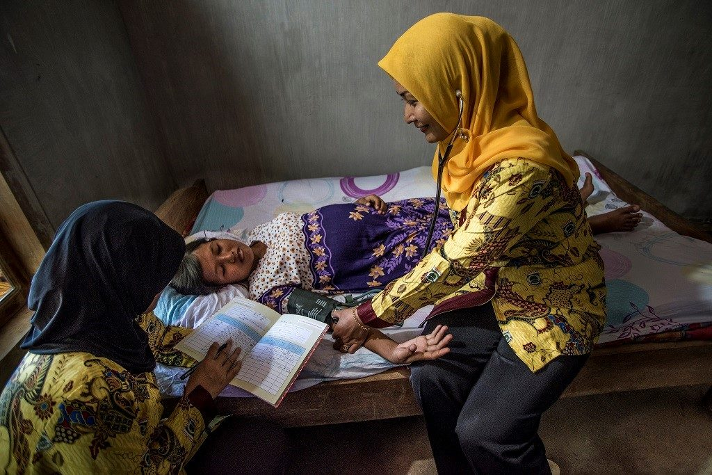 In Indonesia, a pregnant woman has her blood pressure taken while a nurse aid records data.