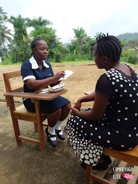 Linda Kharke, a family planning peer provider, with a client on the campus of the Esther Bacon School of Nursing and Midwifery.