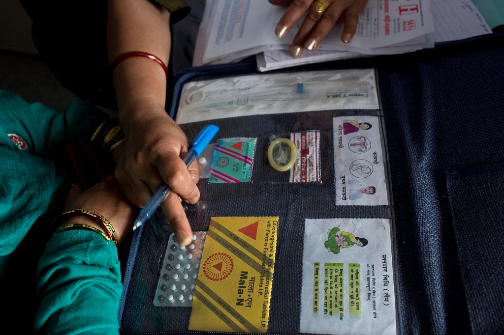 A doctor shows women available family planning methods at District Female Hospital in Pauri, India.
