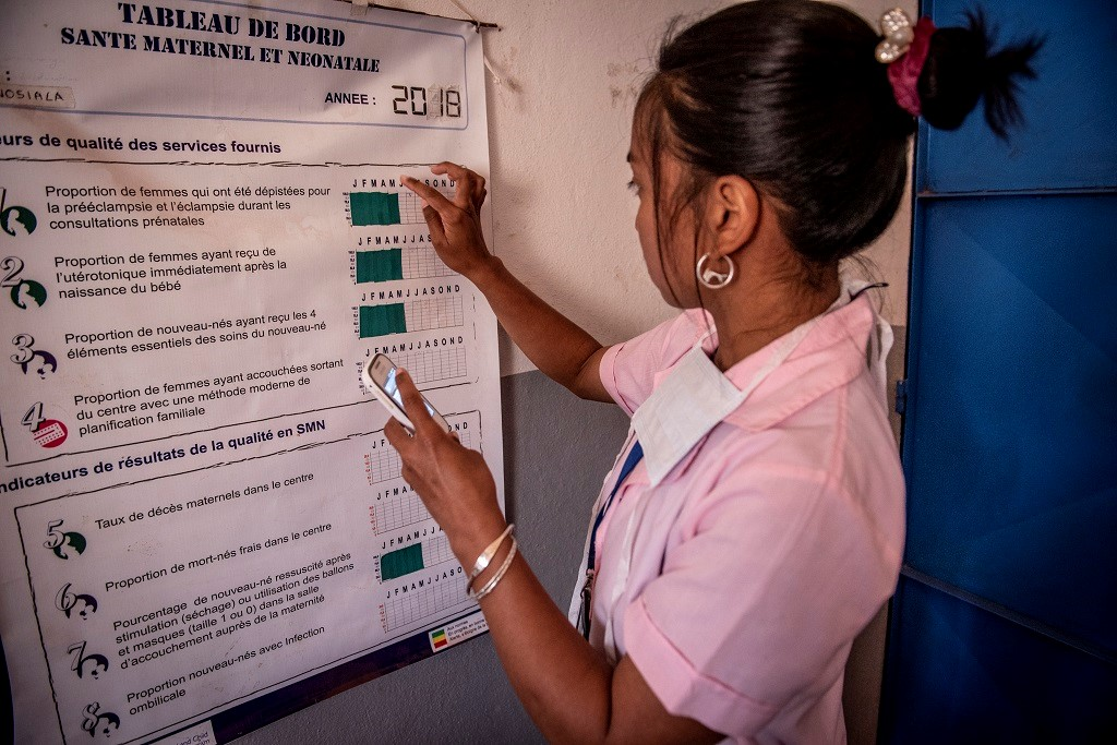 At a health clinic in Madagascar, a student nurse puts information on a dashboard