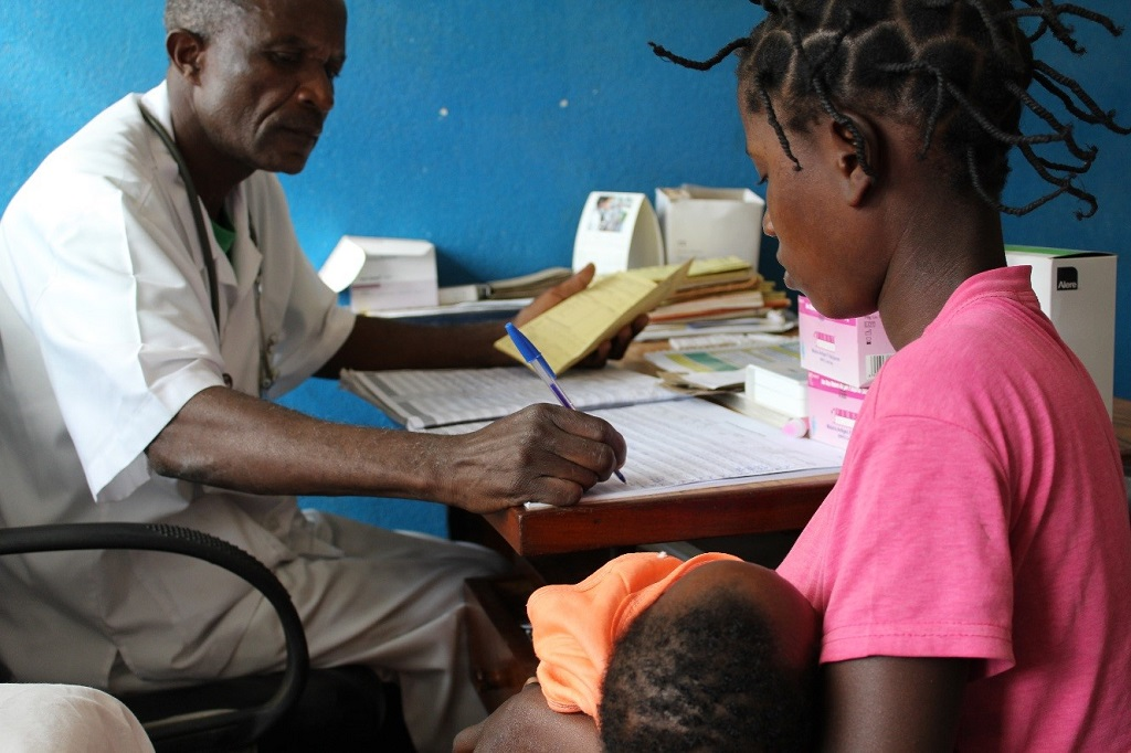 During a sick child consultation, health technician Zacarias Morruela fills in a new child health registration book.