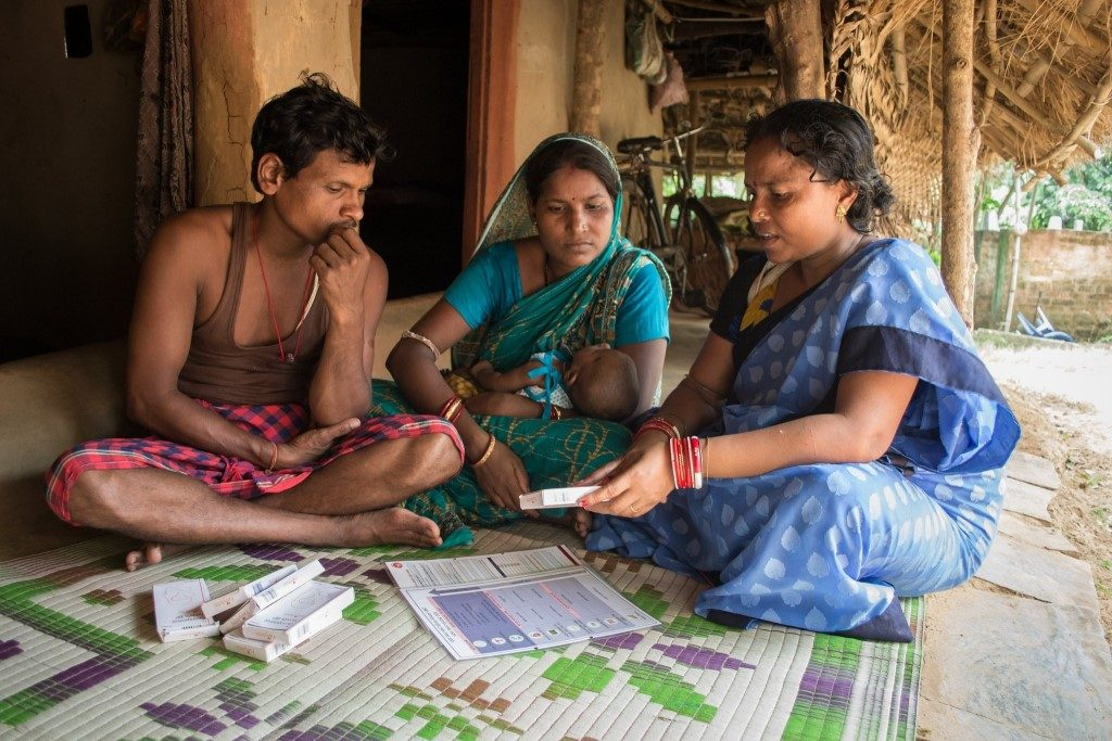 Couple with baby in India discussing birth control methods
